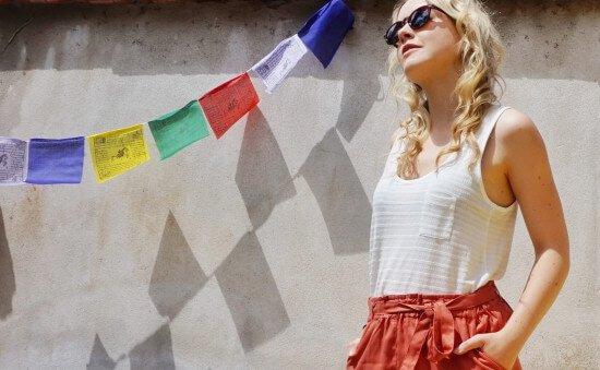 Foto von Stefanie Bock in weißem Top und orange farbener Shorts vor Außenwand
