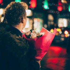Mann mit Blumen in Abenddämmerung auf der Straße