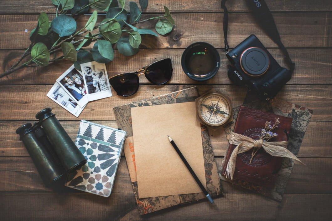 Wichtige Gegenstände für einen nachhaltigen Urlaub: Kamera, Papier, Fotos, Sonnenbrille und Fernglas