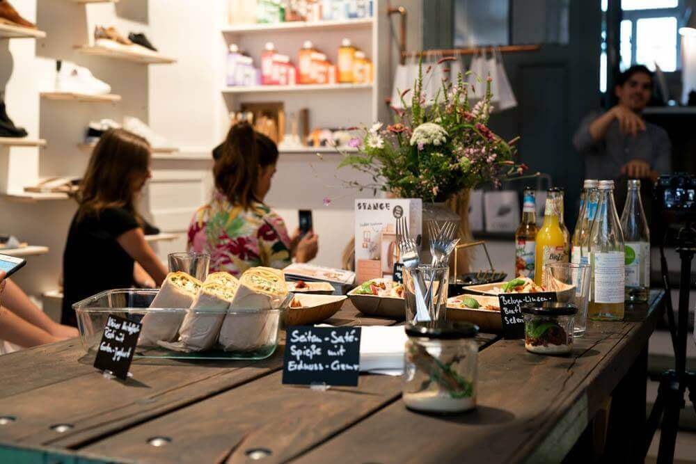 Teilnehmer hinter Tisch im LOVECO Vegan Shoes Laden in Berlin Kreuzberg