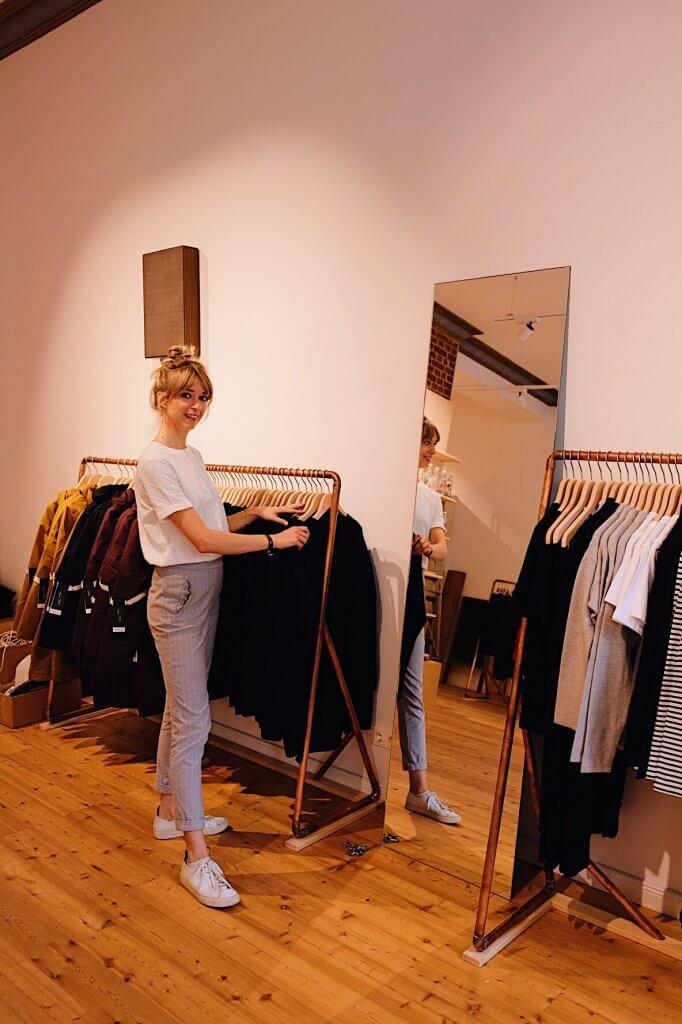 Frau steht an Kleiderstange