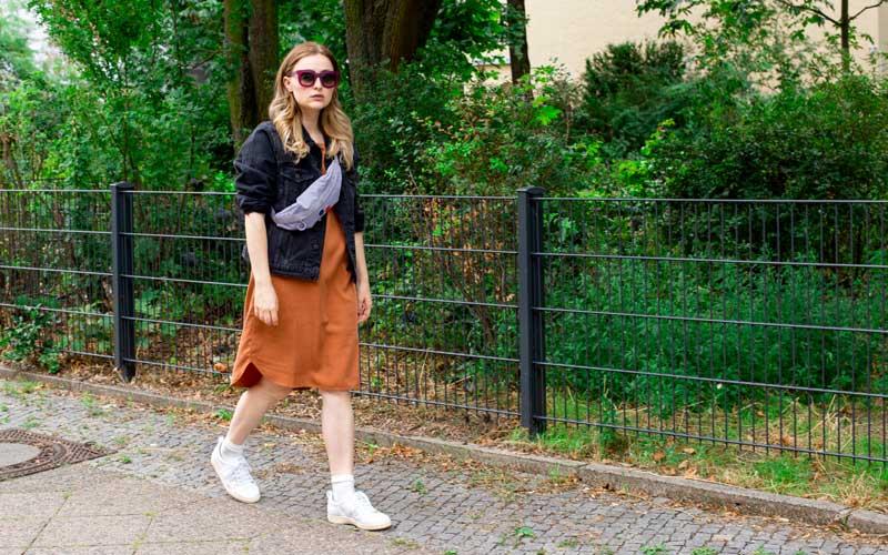 Frau trägt Kleid, Bauchtasche und Sonnenbrille