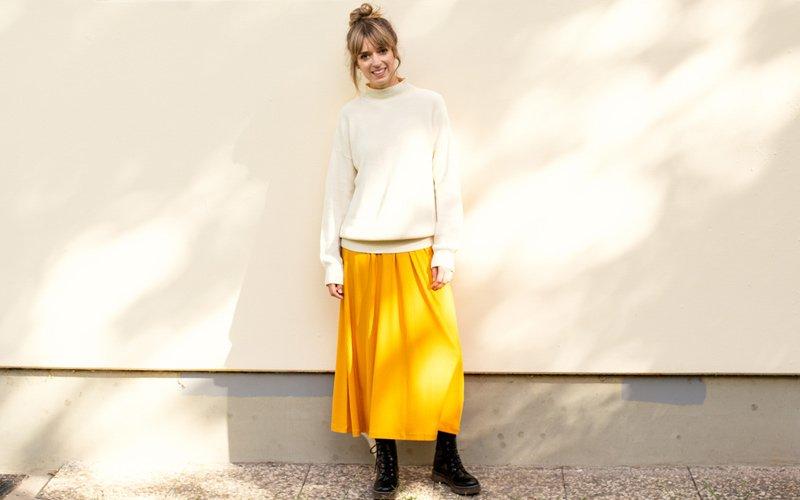 Frau trägt gelbes Kleid und beigen Strickpulli