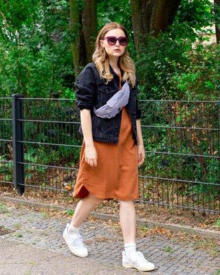 Frau in braunem Kleid und schwarzer Jeansjacke