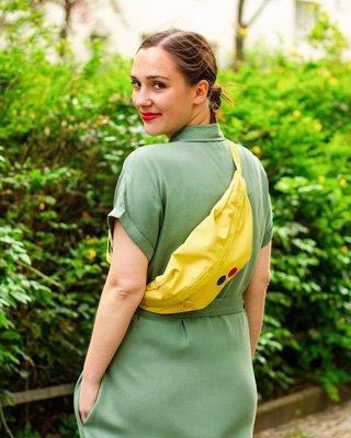 Frau trägt grünes Kleid und gelbe Bauchtasche