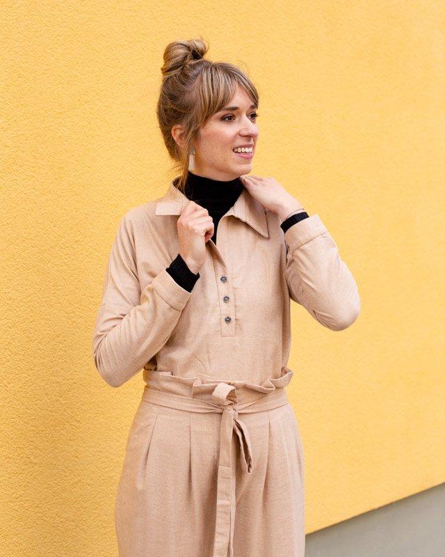 Frau trägt beigen Zweiteiler und schwarzen Rollkragenpullover