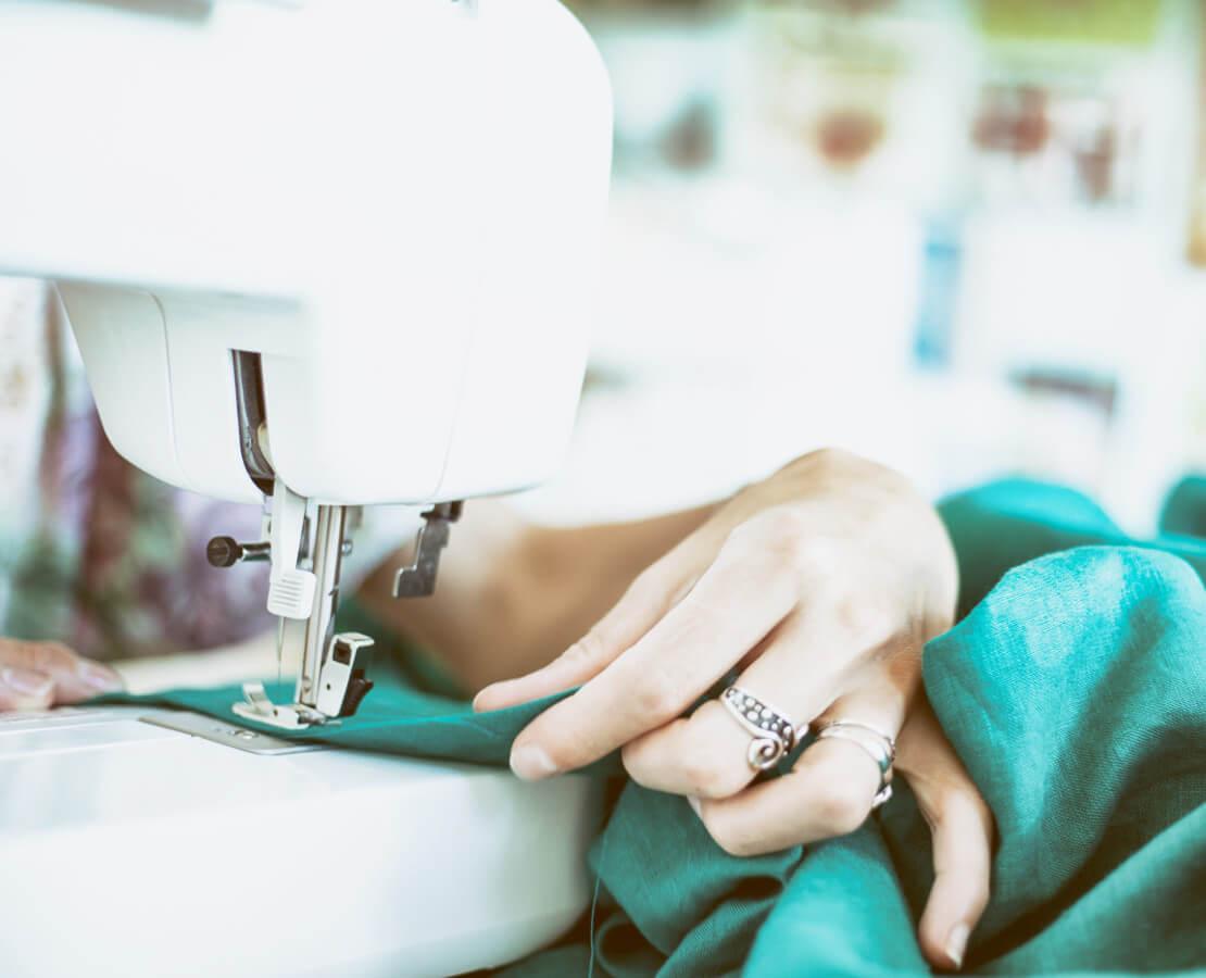 Nahaufnahme einer Frau an der Nähmaschine
