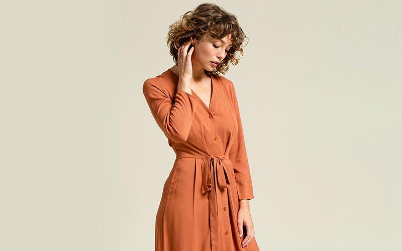 Frau trägt braunes Kleid aus Tencel.