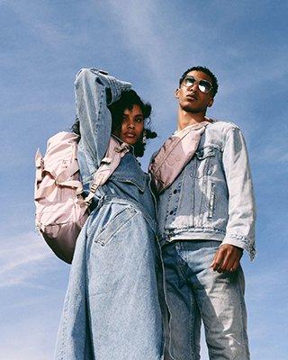 Mann und Frau mit Rucksäcken stehen vor blauem Hintergrund