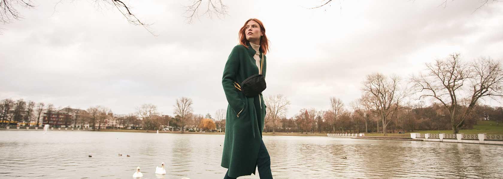 Frau in grünem Mantel vor See