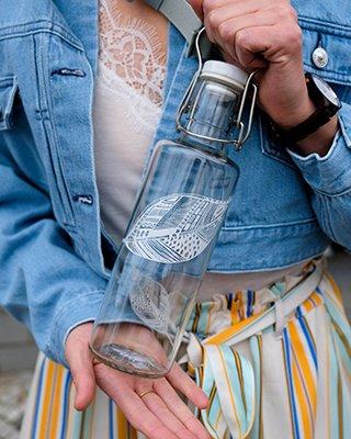 Frau hält Glasflasche in den Händen