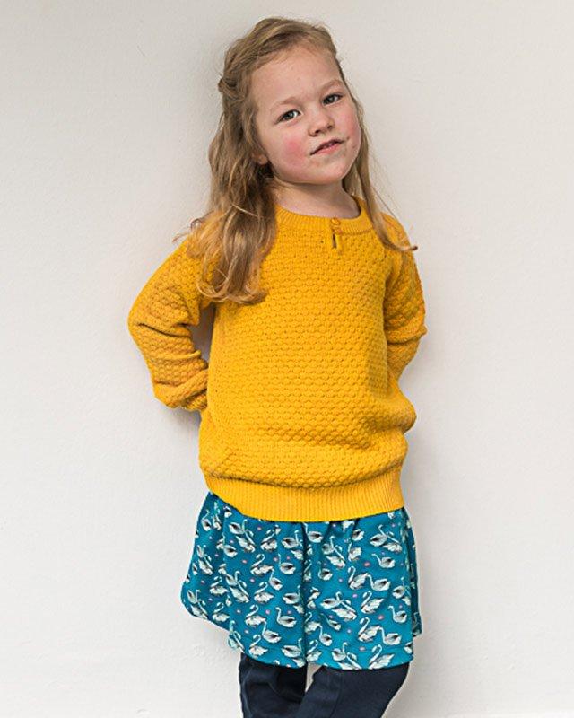 Mädchen trägt gelben Pulli aus Biobaumwolle