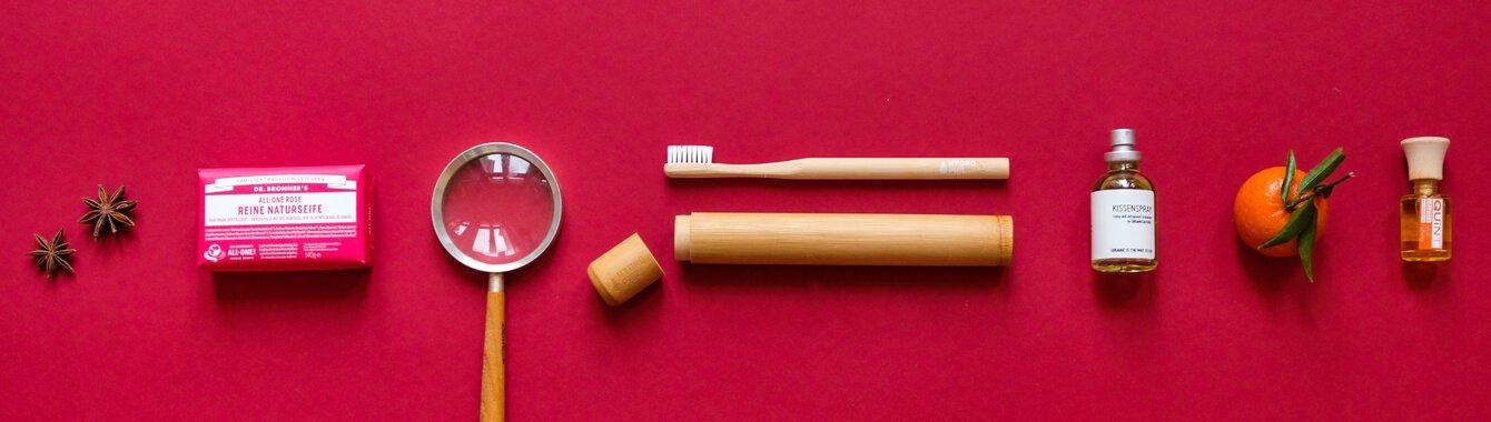 Seife, Holzzahnbürste, Zahnbürstenetui, Kissenspray und Raumduft liegen auf rotem Hintergrund