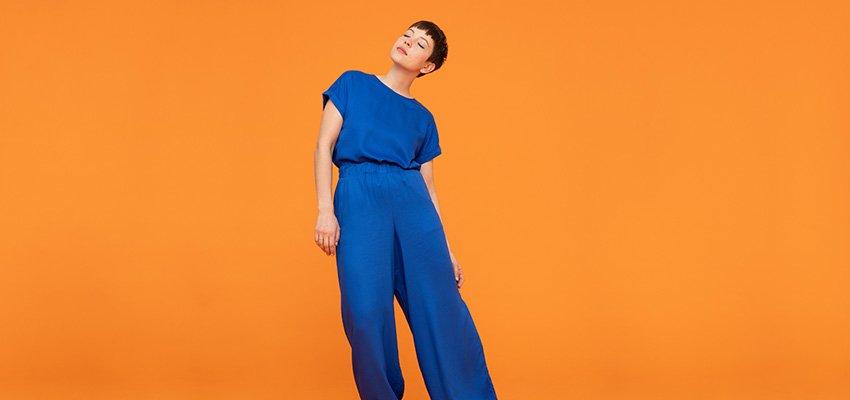 Frau in blauem Outfit steht vor orangener Wand