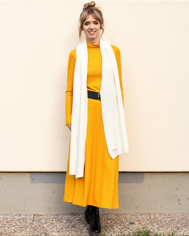 Frau trägt gelbes Kleid und beigen Strickpullover