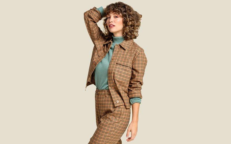 Frau trägt karierte Hose und Jacke