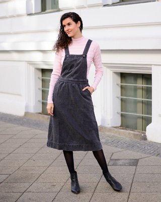Frau trägt Jeanskleid und rosa Longsleeve