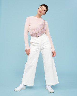 Frau trägt weiße Hose und rosa Pullover