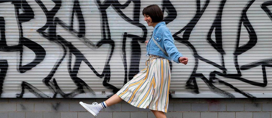 Frau in sommerlichem Outfit steht vor Graffiti