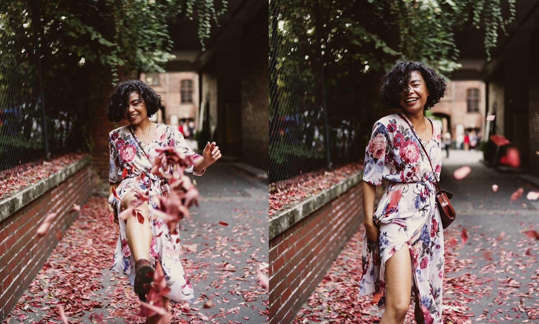 Frau in Blumenkleid tanzt durch Laub
