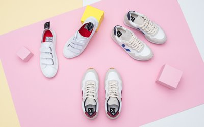 Weiße Sneaker liegen auf farbigen Hintergrund