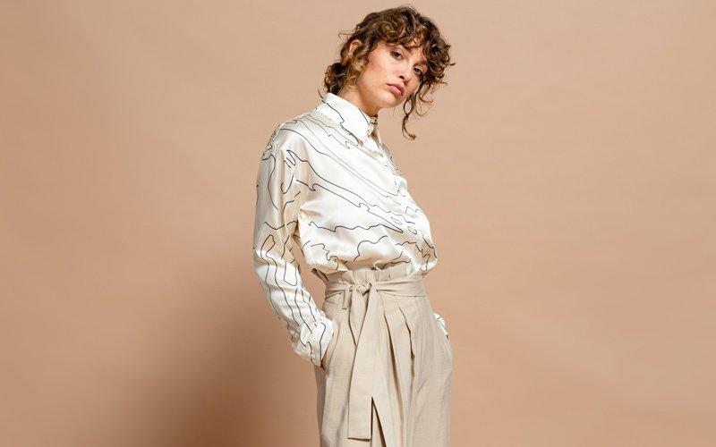 Frau trägt Faltenhose und weiße Bluse