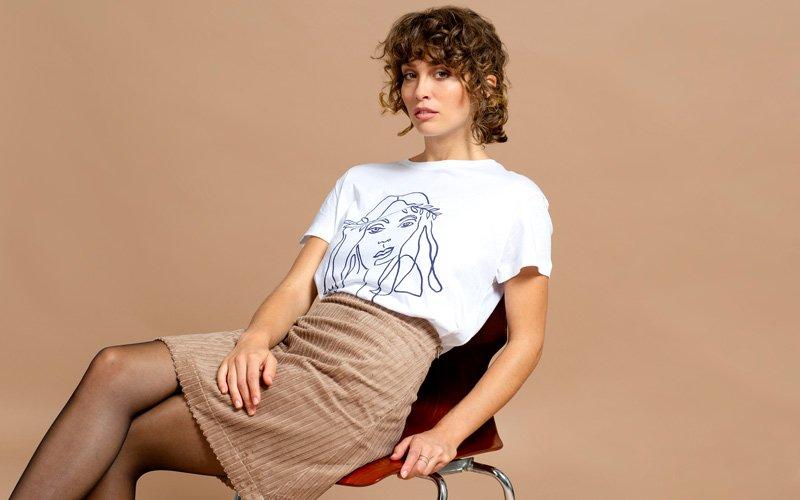 Frau trägt beigen Cordrock und weißen T-Shirt