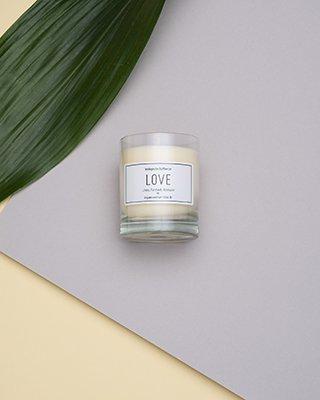 Kerze mit LOVE Aufschrift auf grauem Hintergrund