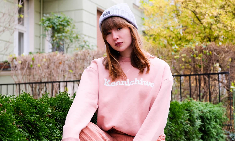 Frau trägt rosa Sweater und graue Mütze