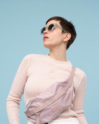 Frau trägt blaues Kleid vor rosa Hintergrund