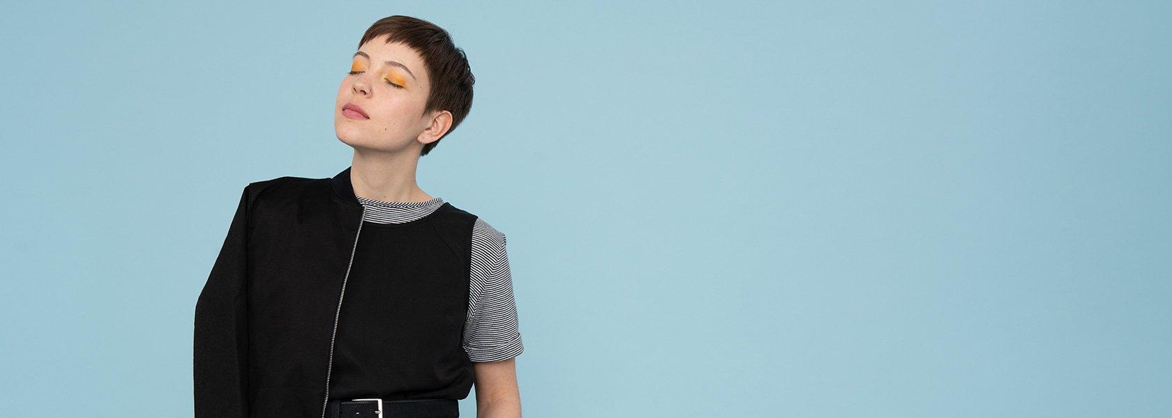 Frau mit schwarzem Top und gelbem Lidschatten steht vor blauer Wand