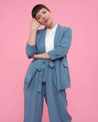 Frau trägt blauen Damenanzug und weiße Bluse