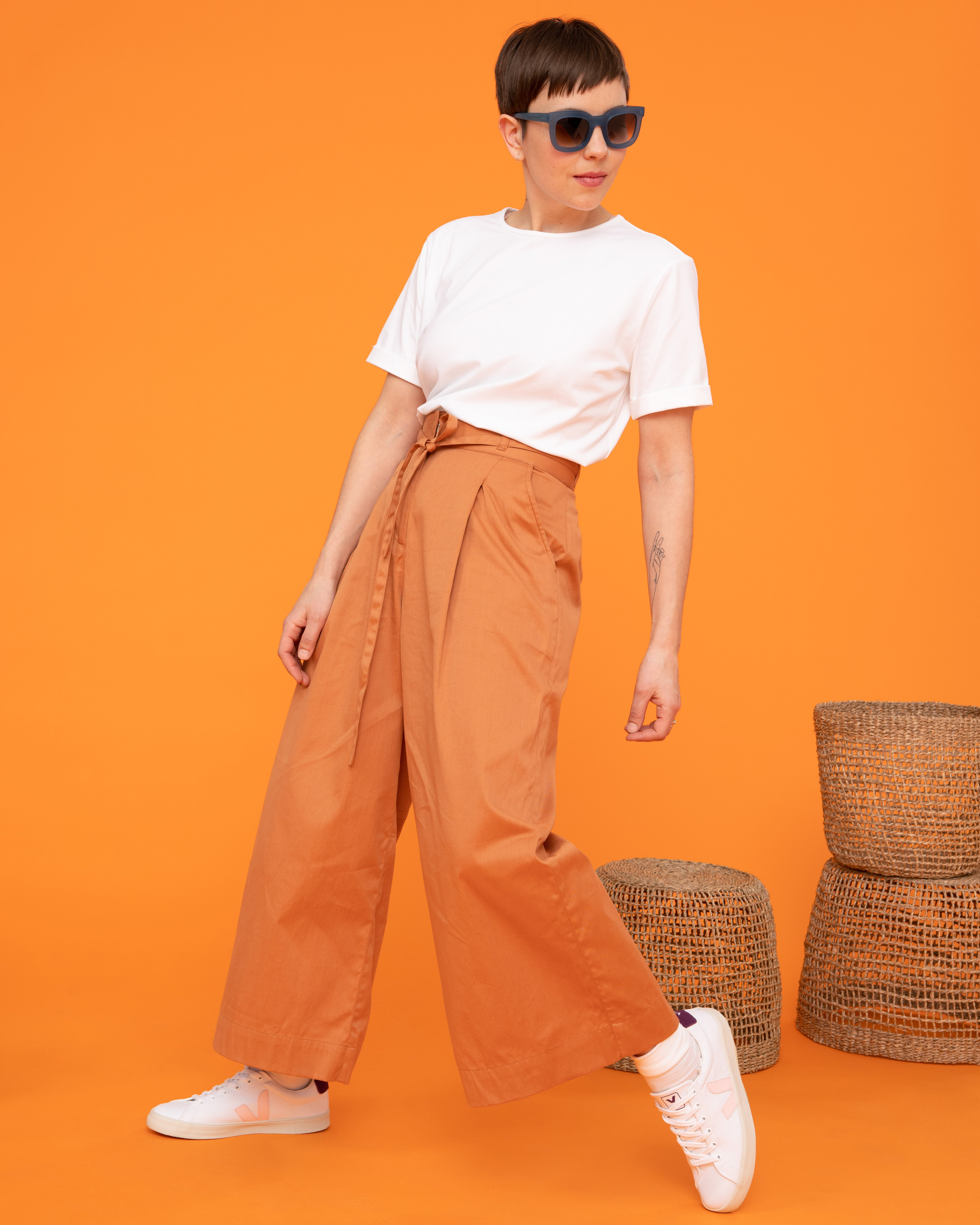 Frau trägt weißes Shirt und orangefarbene Hose