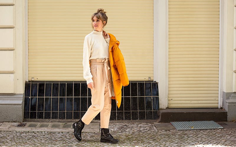Frau trägt beige Hose, Strickpulli und veganer Mantel