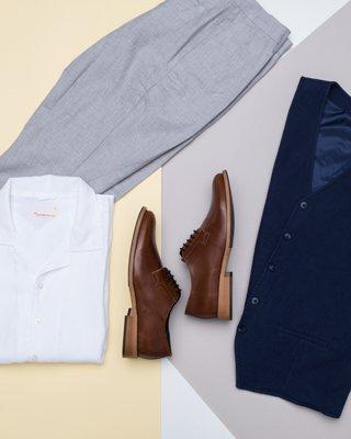 Braune Schuhe, weißes hemd und graue Chino liegen auf farbigen Hintergrund