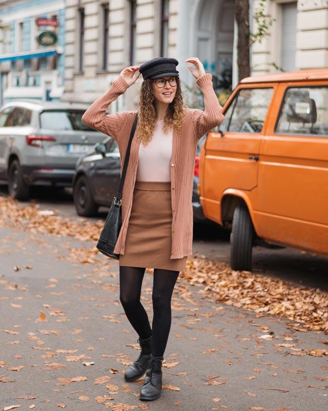 Frau trägt braunen Rock und rosa Cardigan