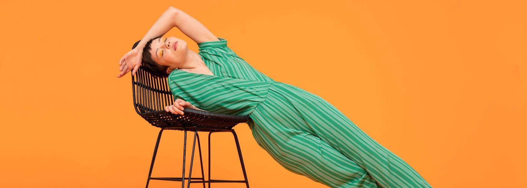 Frau mit grünem Jumpsuit und orangenem Lidschatten