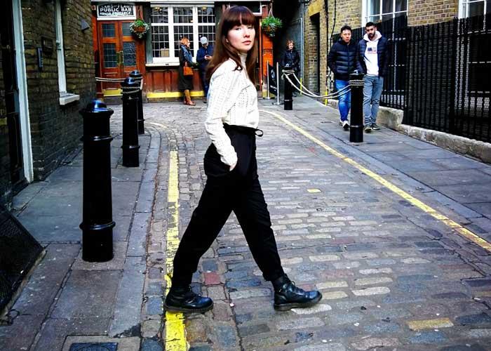 Frau trägt schwarze Hose und weiße Bluse