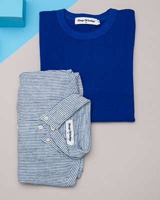 Blaues Hemd liegt auf blauem Pullover