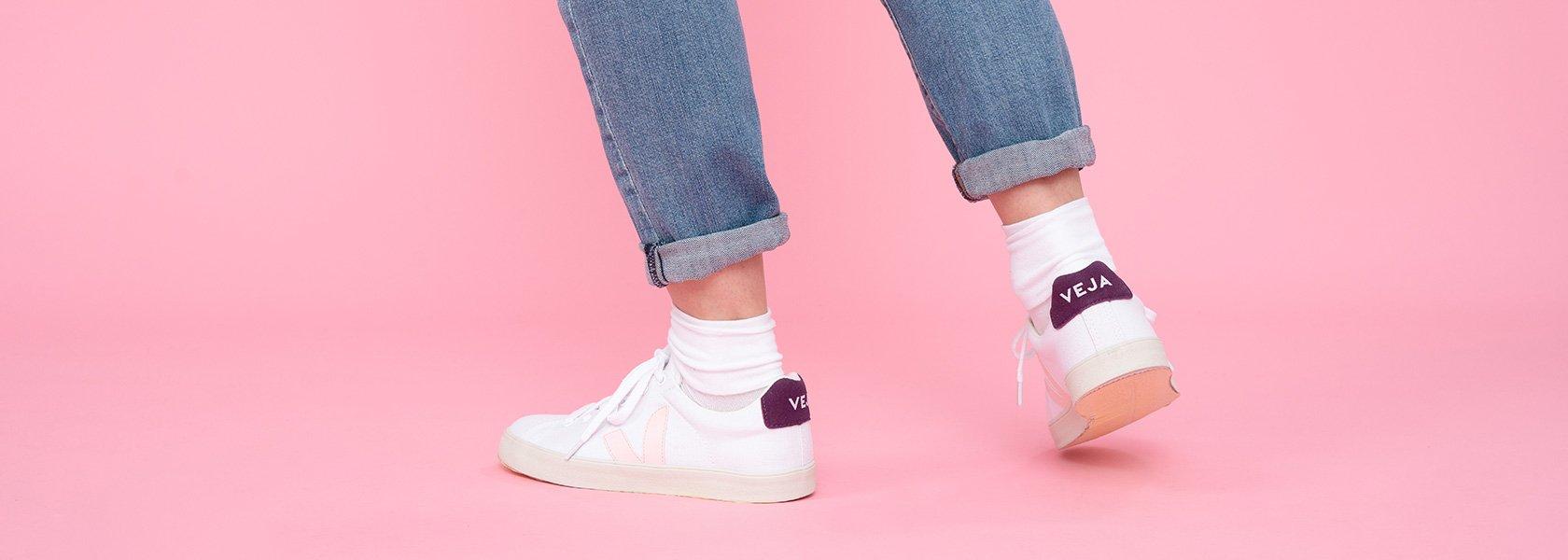 Frau mit weißen Sneakern steht auf rosa Untergrund