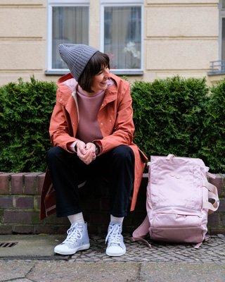 Frau trägt Regenjacke und Rucksack