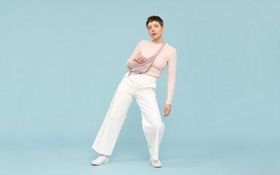 Frau trägt weiße Culotte und rosa Pullover