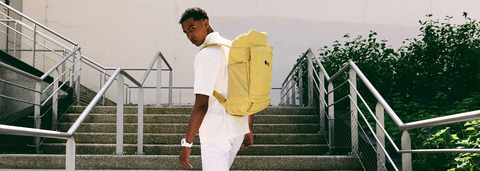 Mann läuft Treppe hoch und trägt gelben Rucksack