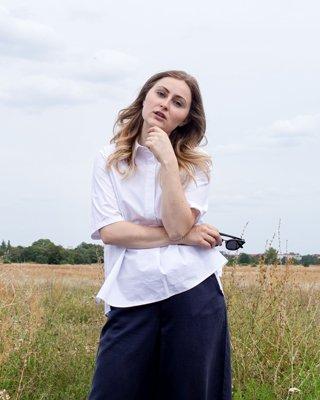 Frau mit weißer Bluse, blauer Hose und Sonnebrille vor Feld
