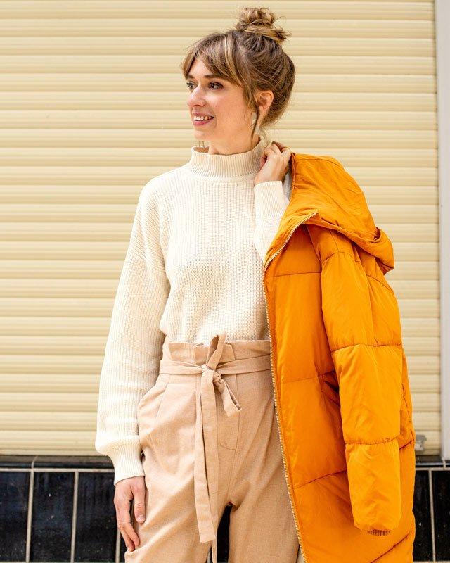 Frau trägt beige Hose, Pullover und eine gelbe Jacke
