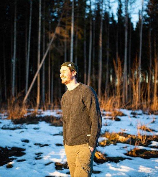 Mann mit Mütze vor Wald
