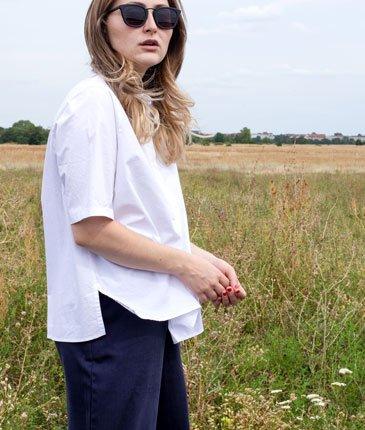 Frau trägt weiße Bluse und Culottes von ARMEDANGELS