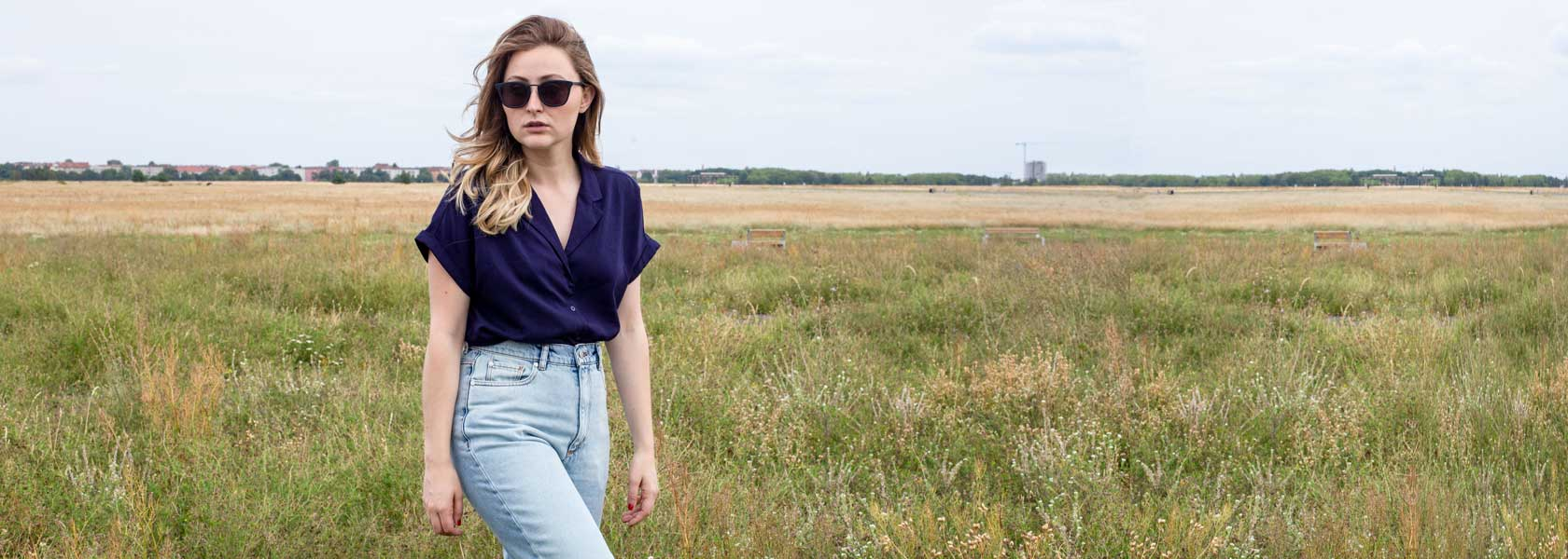 Frau trägt Jeans und Bluse und läuft über Feld