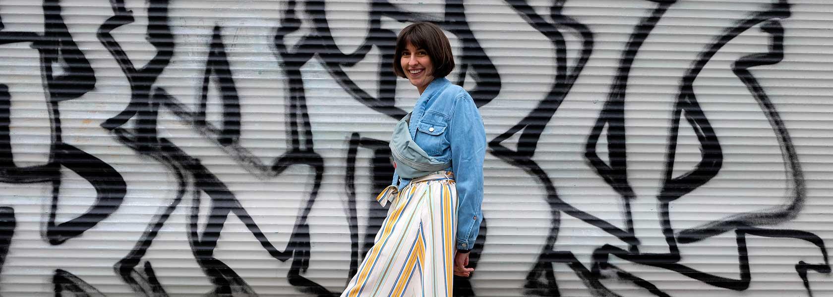 Frau in sommerlichem Outfit steht vor Graffitiwand